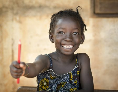 Holding a red pencil, a young African schoolgirl poses for a shot showing her school things in Bamako, Mali.